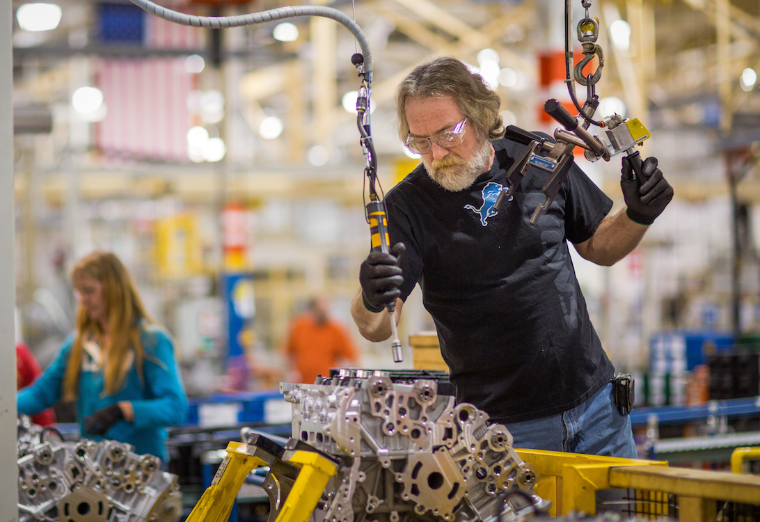 General Motors Flint Engine Operations employee Jim Buckel places an engine head on a 6-cylinder LLT block Wednesday, Nov. 20, 2013 at the plant in Flint, Michigan.